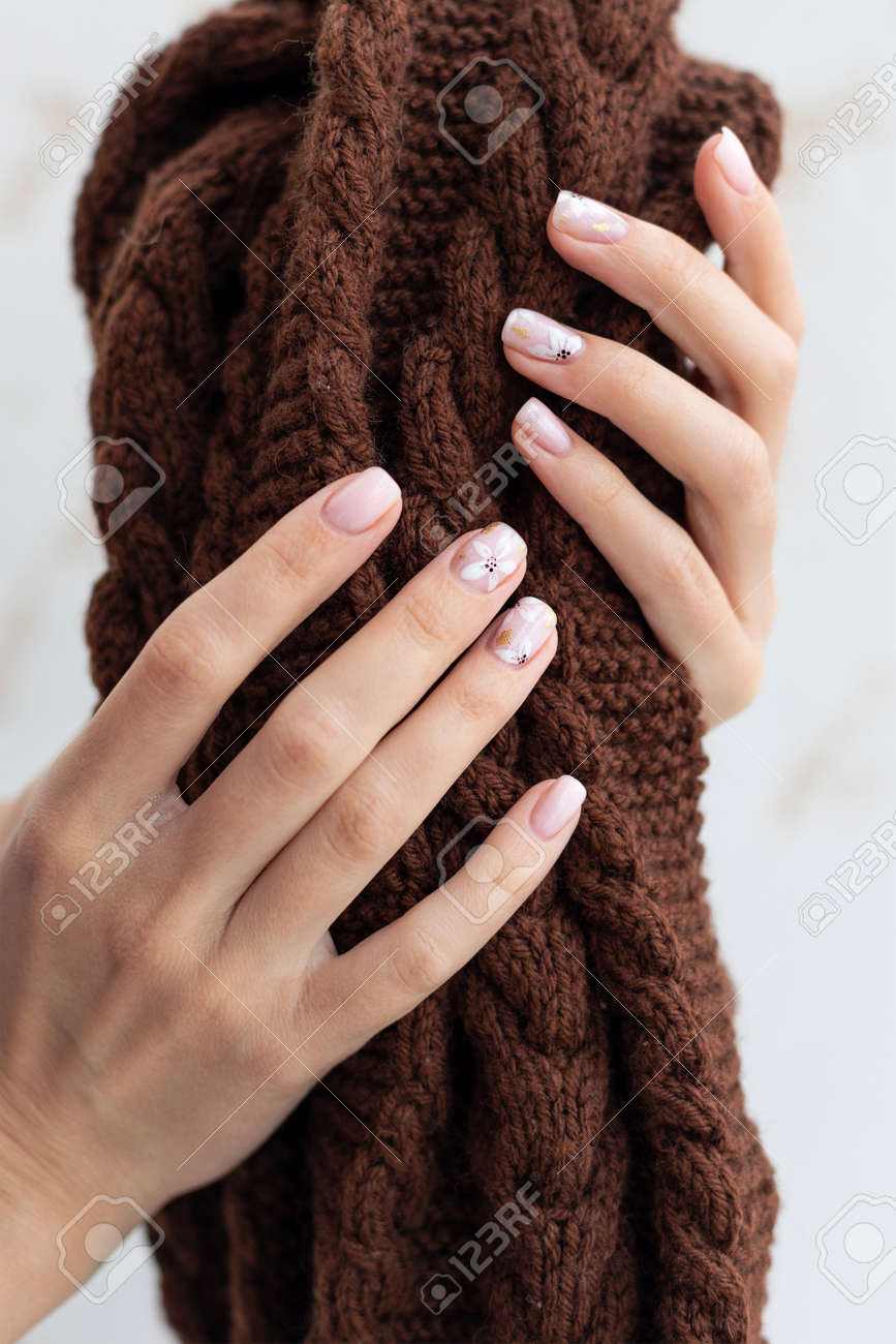 Female hand manicure close up view with warm sweater on light background. - 163588262