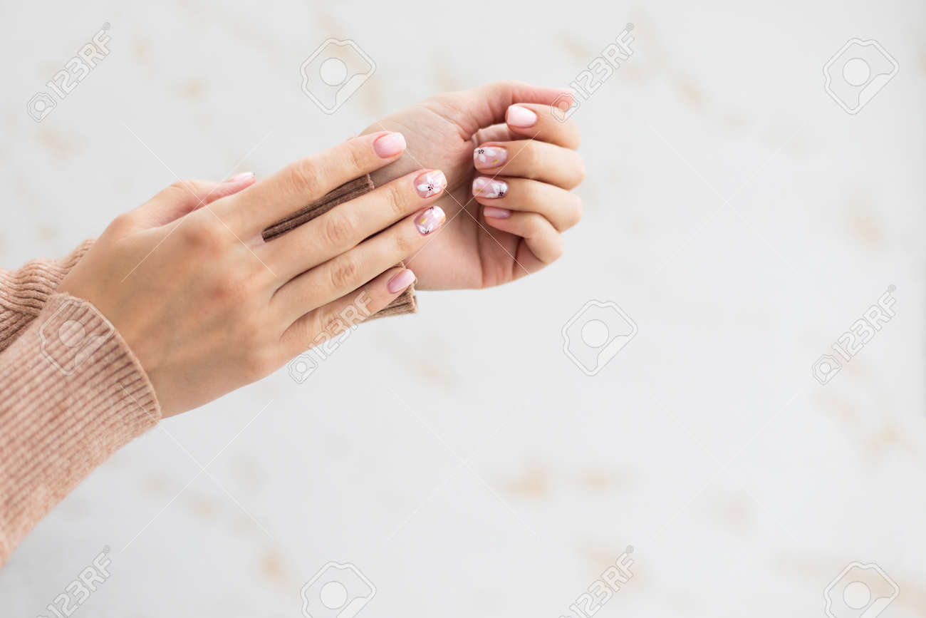 Female hand manicure close up view with warm sweater on light background. - 163755204