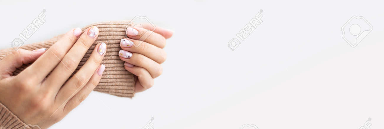 Female hand manicure close up view with warm sweater on light background. - 163755327