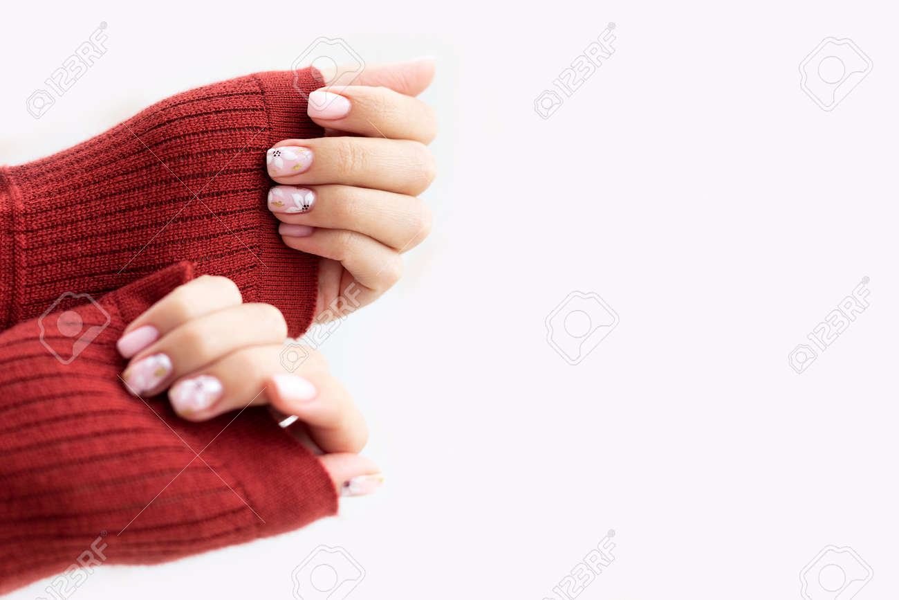 Female hand manicure close up view with warm sweater on light background. - 163755482