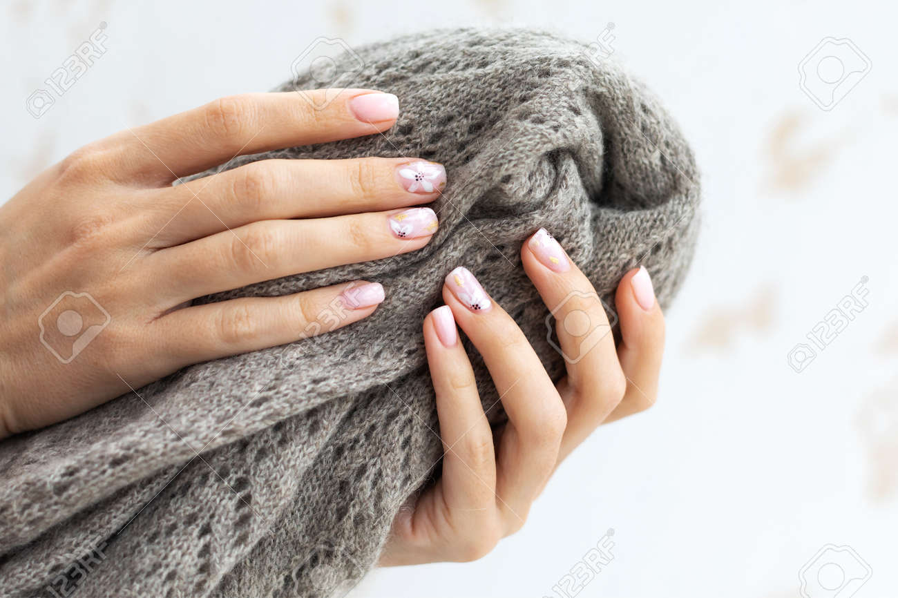 Female hand manicure close up view with warm sweater on light background. - 163755322