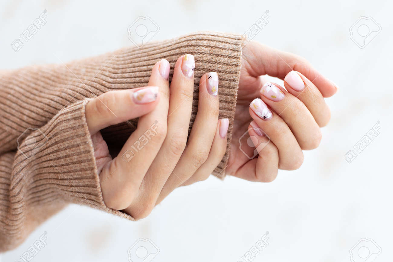 Pastel beige manicure on the light background. Manicured nails and soft hands skin with copy space. Womans hands in warm sweater. - 166315522