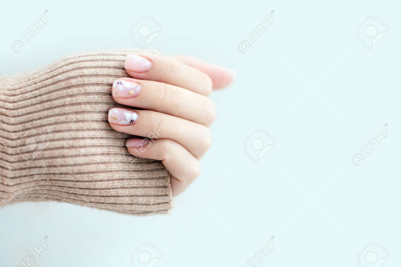 Pastel beige manicure on the light background. Manicured nails and soft hands skin with copy space. Womans hands in warm sweater. - 166364005