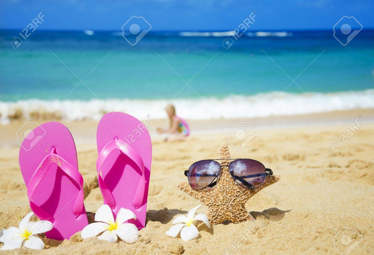 f940e6281e68ba Flip flops and starfish with sunglasses with tropical flowers on sandy beach  with playing girl by