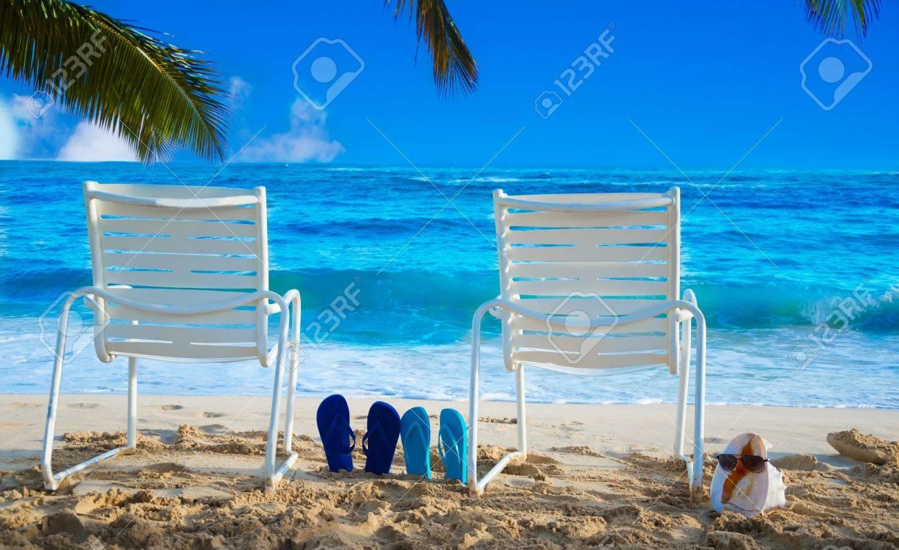 Due sedie a sdraio bianche sotto foglie di palma al mare con le