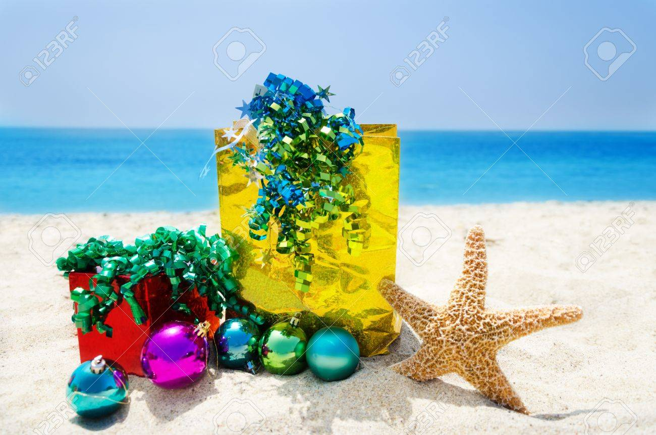 Starfish with Christmas balls, gift box and gift bag on sandy beach in sunny day- holiday concept Stock Photo - 21611741