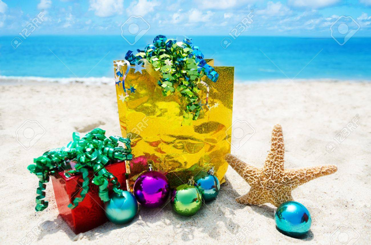 Starfish with gift box and bag and christmas balls on sandy beach in sunny day- holiday concept Stock Photo - 21598592