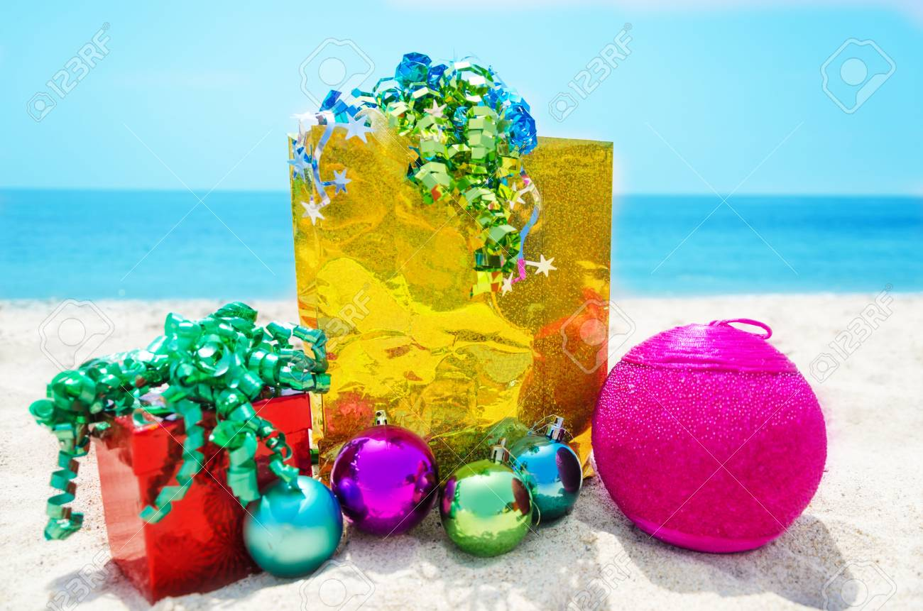 Gold gift bag and red gift box with Christmas balls on sandy beach in sunny day- holiday concept Stock Photo - 21598593