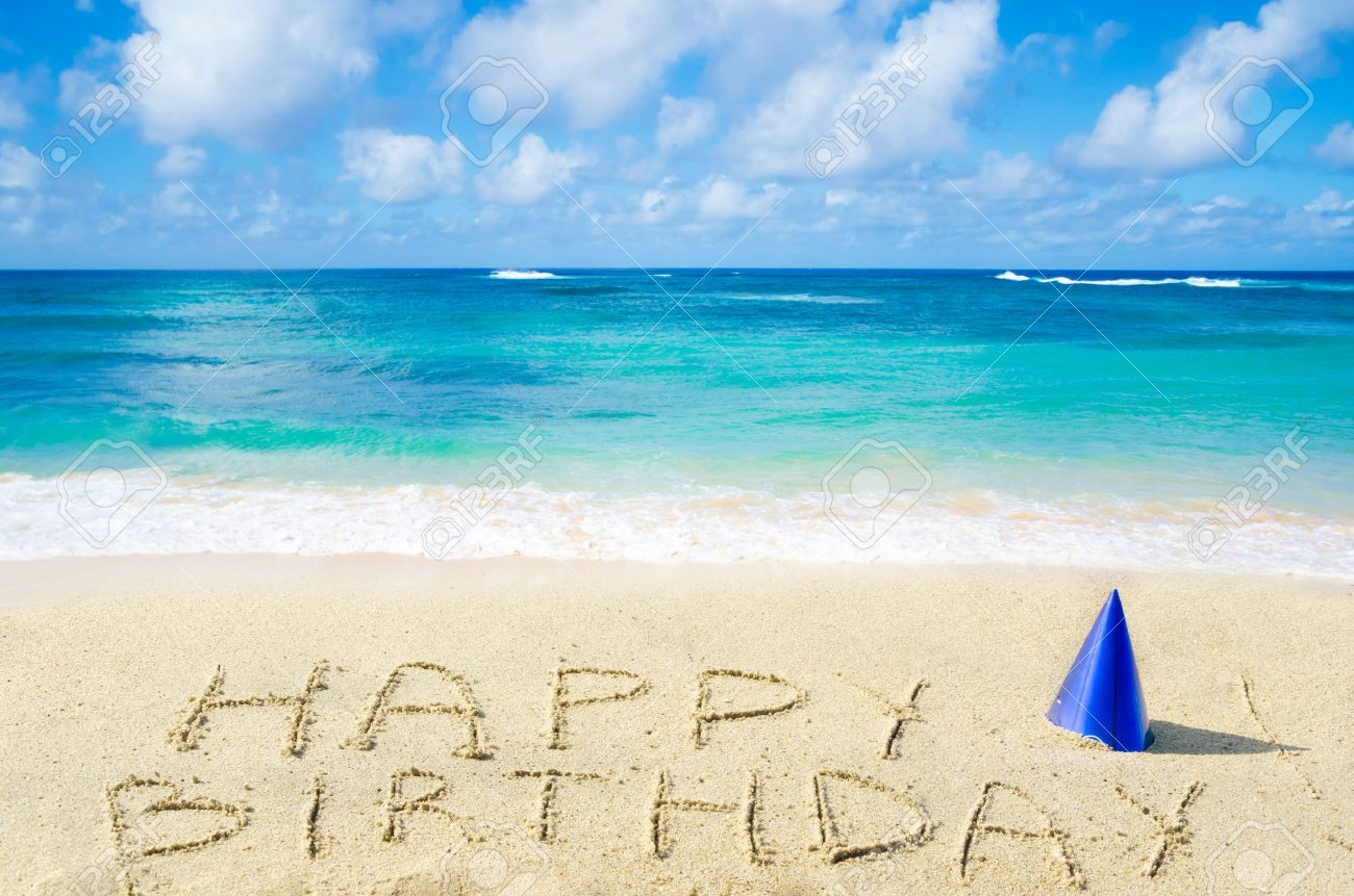 Sign Happy Birthday With Hat On The Sandy Beach By Ocean Stock