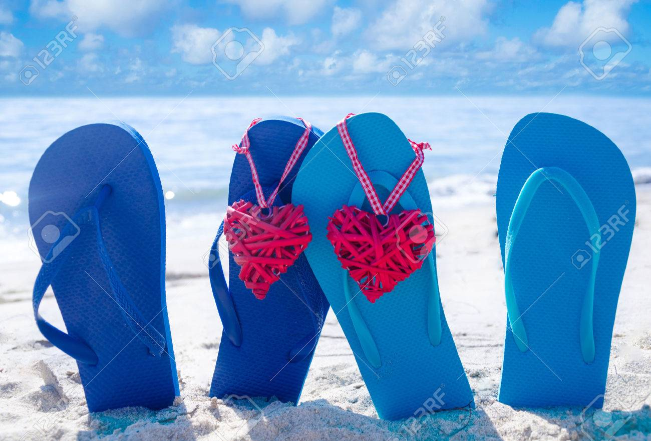 f96a24bad60b Flip flops with two heart shapes on the sandy beach by the ocean Stock  Photo -