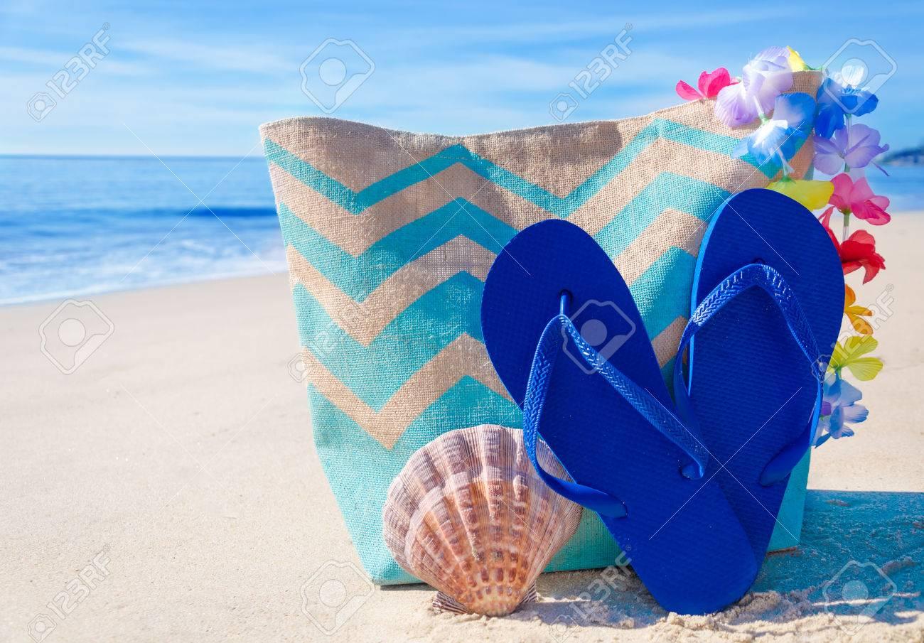 d35e1d7c79fda Beach bag with seashell and flip flops by the ocean Stock Photo - 26043166