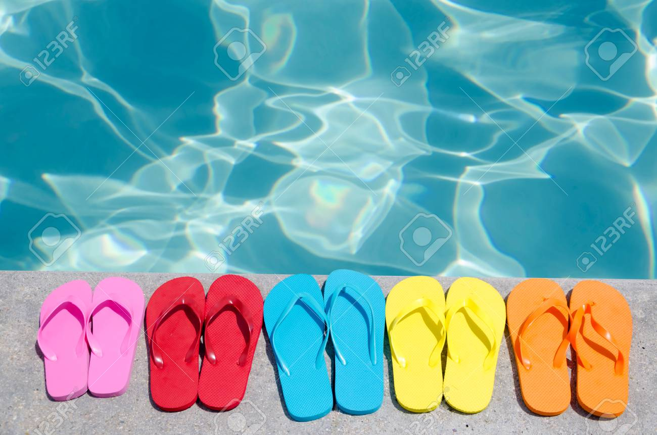 39ca62ad9e4b7f Color flip flops by the swimming pool in sunny day Stock Photo - 28522232