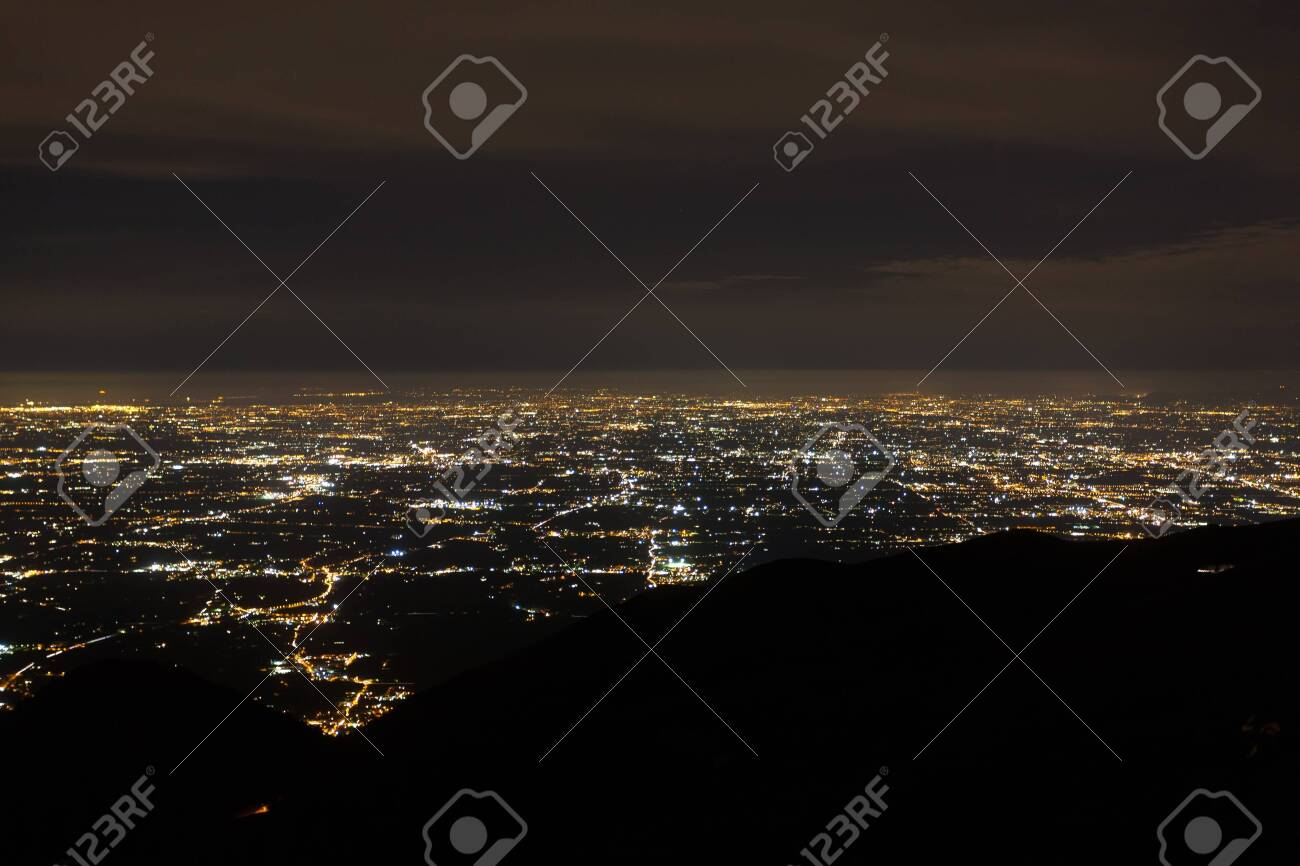 Aerial view of a plain illuminated by electric light. Mount Grappa, Italian landscape - 143525144