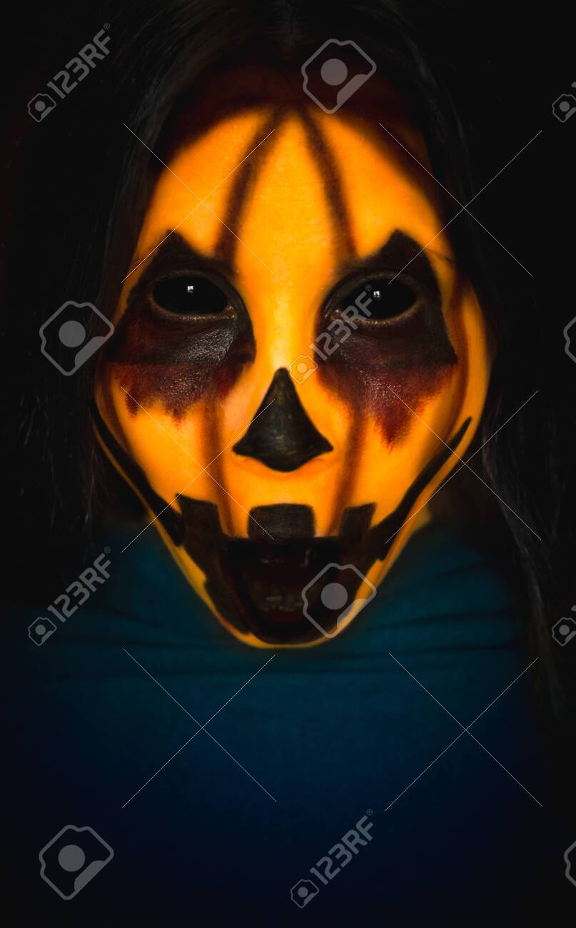 Scary pumpkin face of a halloween creature with opened mouth on dark background. Close-up vertical portrait of a monster with copy space - 130798813