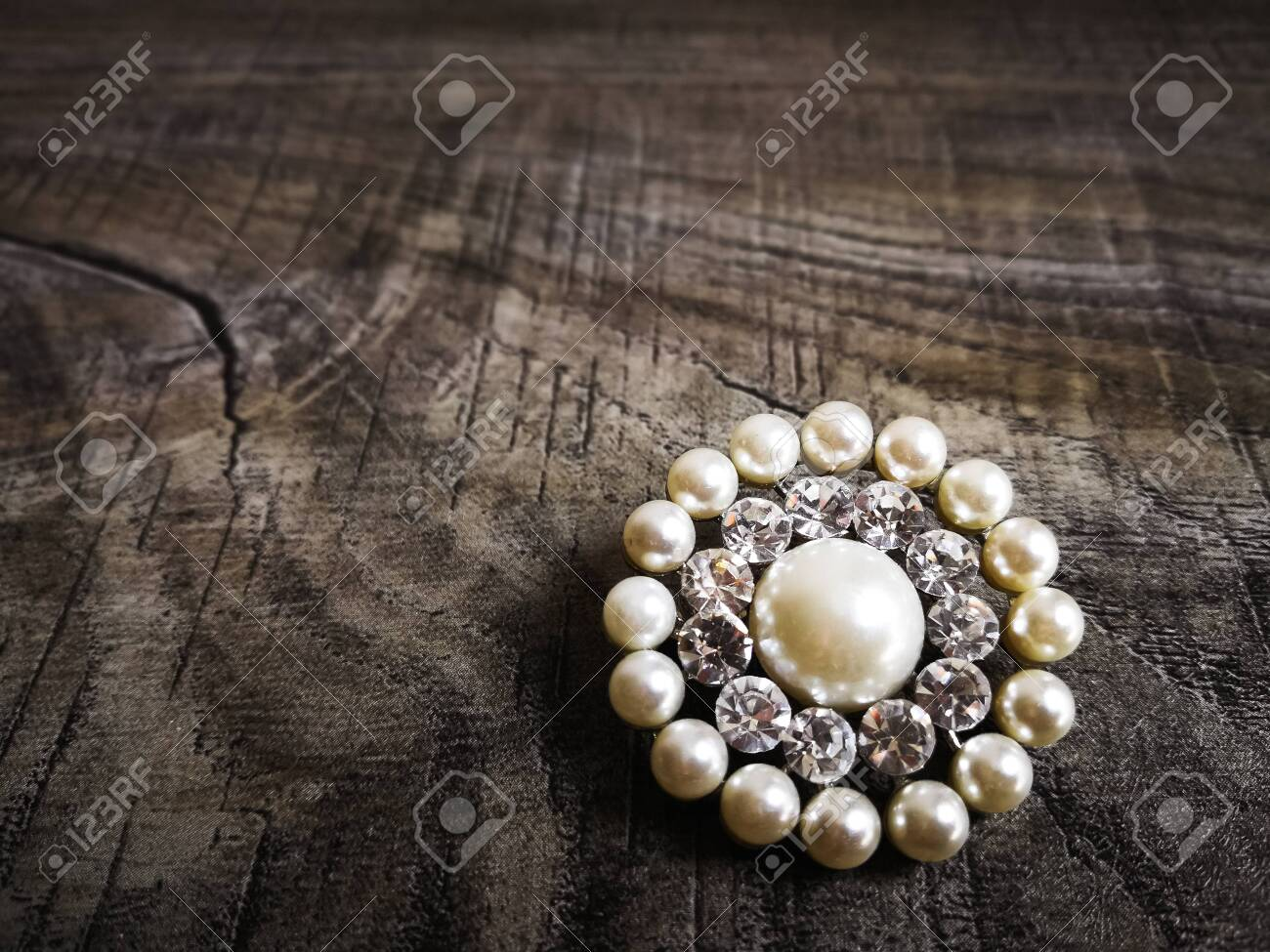 Brooch with white pearl for clothes isolated on wooden background. Brooch with diamond stone. Old precious brooch - 133317325