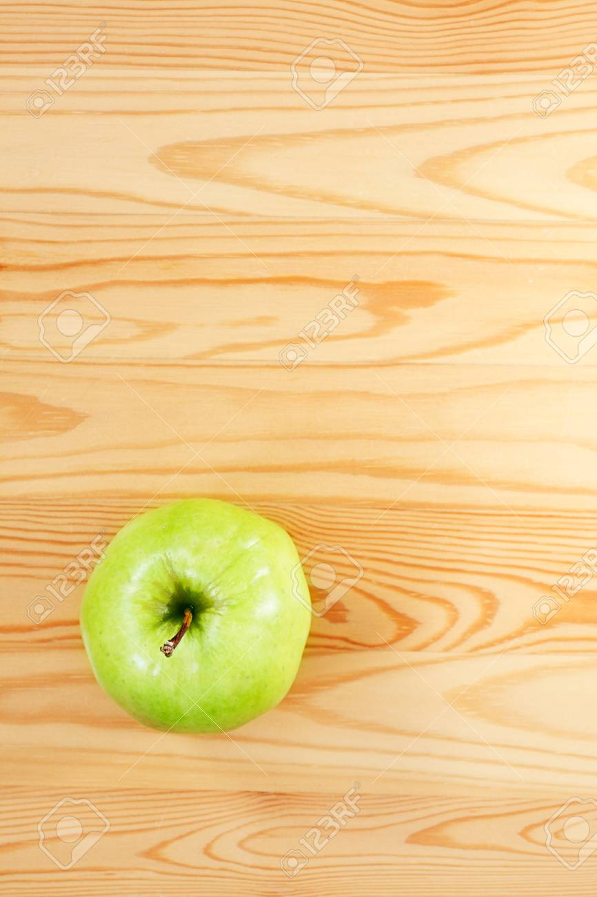Green apple on a light wood  View from the top Stock Photo - 13579170