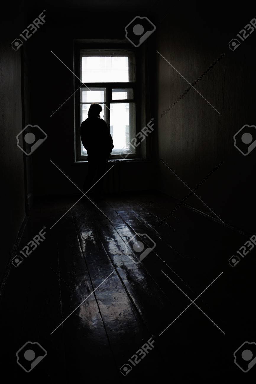Lonely woman at the window in empty old room - 27575733