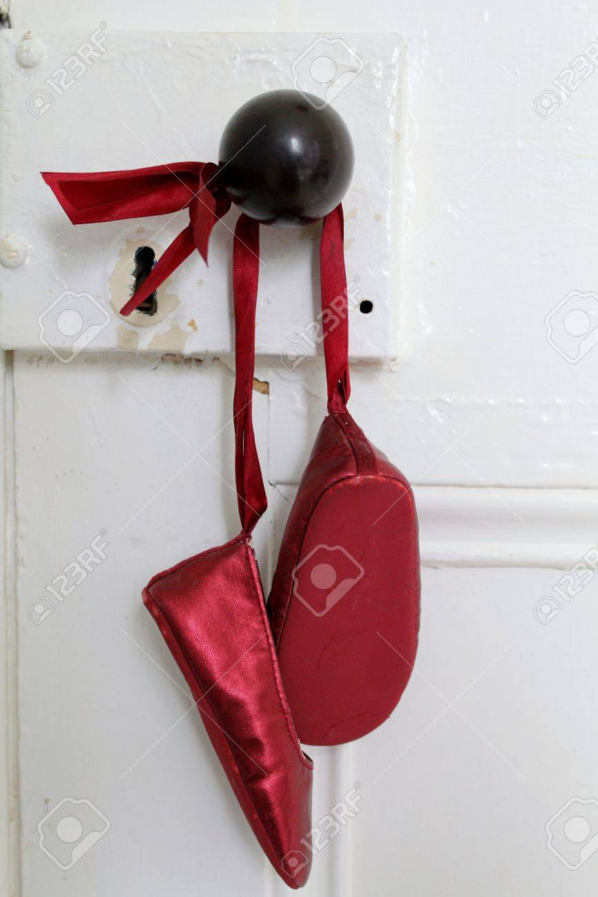 Red Ballet Shoes Hanging On An Old Door With Key Hole Ad Black
