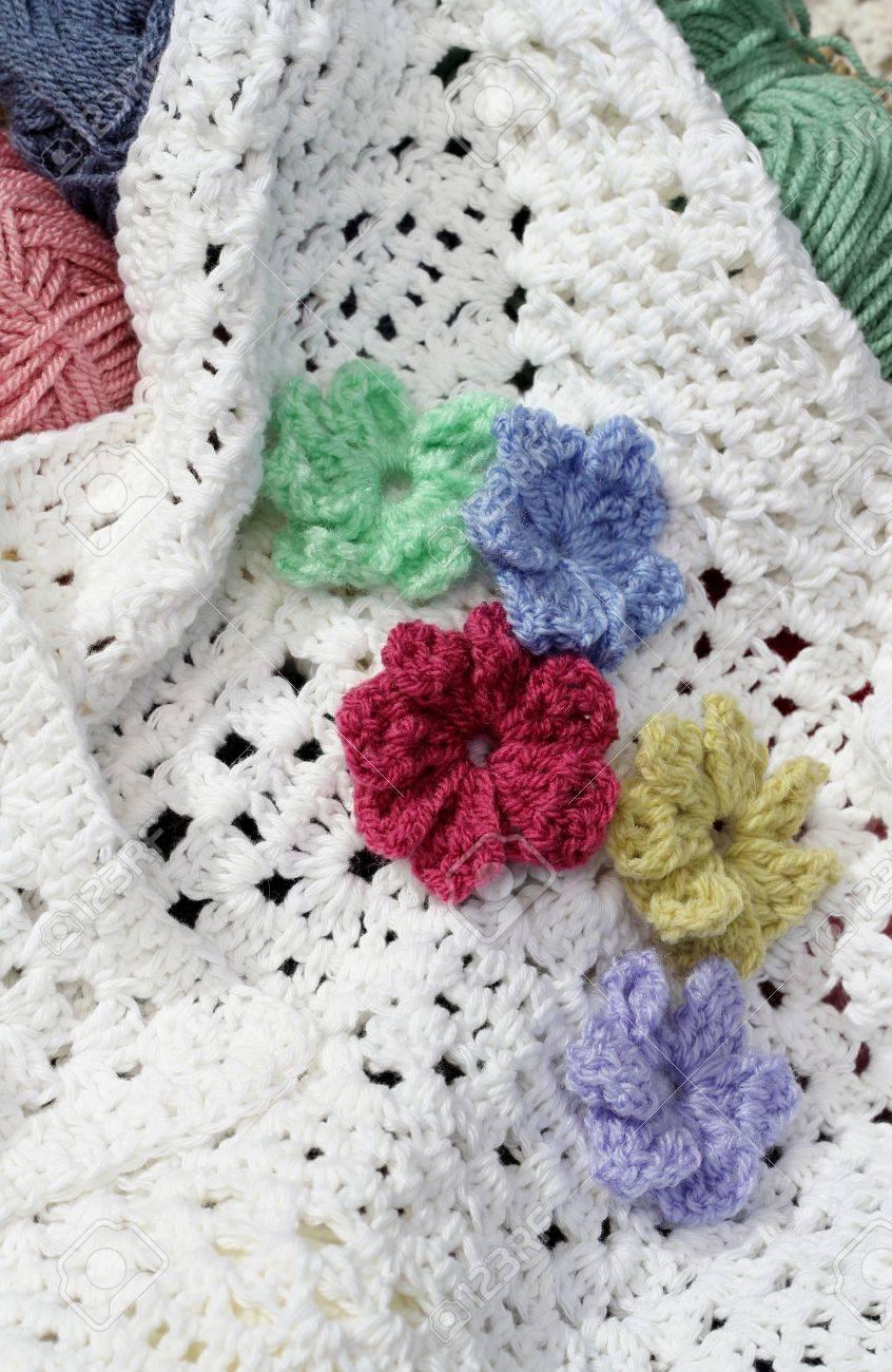 Crocheted Flowers On A White Afghan Crochet Blanket Stock Photo