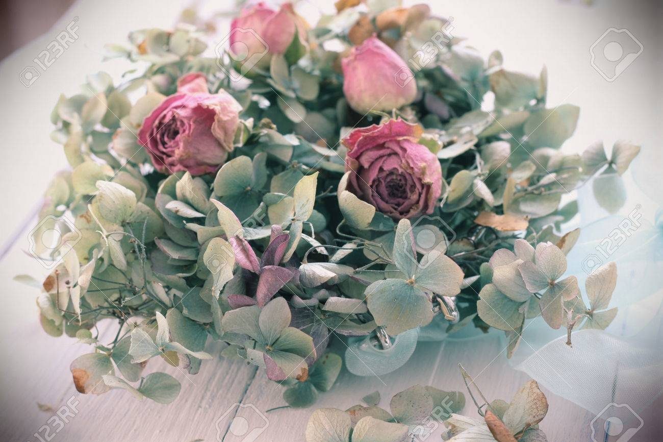Vintage old style image of dried blue hydrangea and pink rose buds a romantic ethereal flower arrangement on white wooden floorboards wedding blue hydrangea and pink rose buds a romantic ethereal flower arrangement on white wooden floorboards wedding bouq