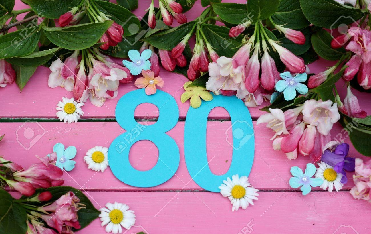 Número 80 En Corte De Papel Turquesa Rodeado De Flores De Primavera De Margaritas Campanas Azules Flores Y Hojas En Un Piso De Madera Pintado De