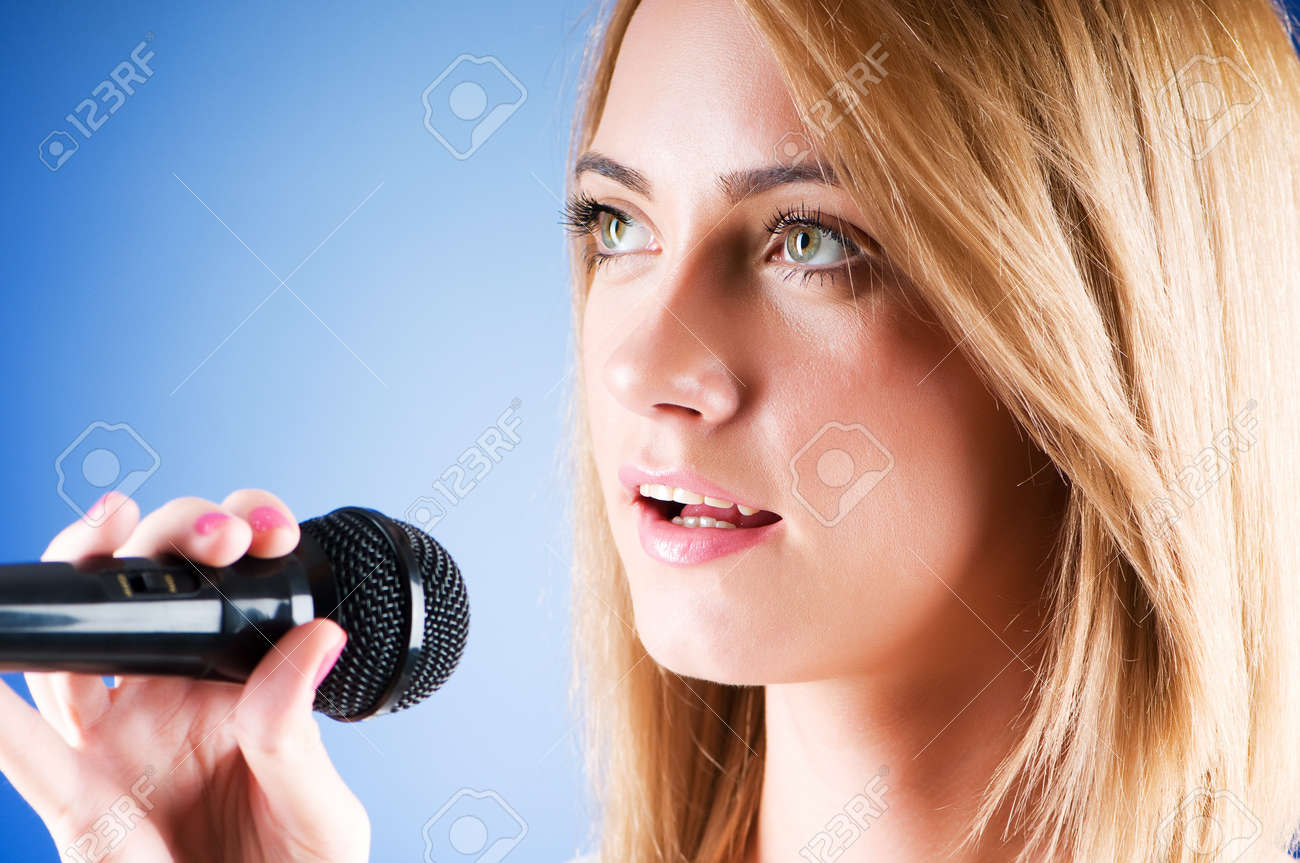 Girl singing with microphone against gradient background Stock Photo - 7941345