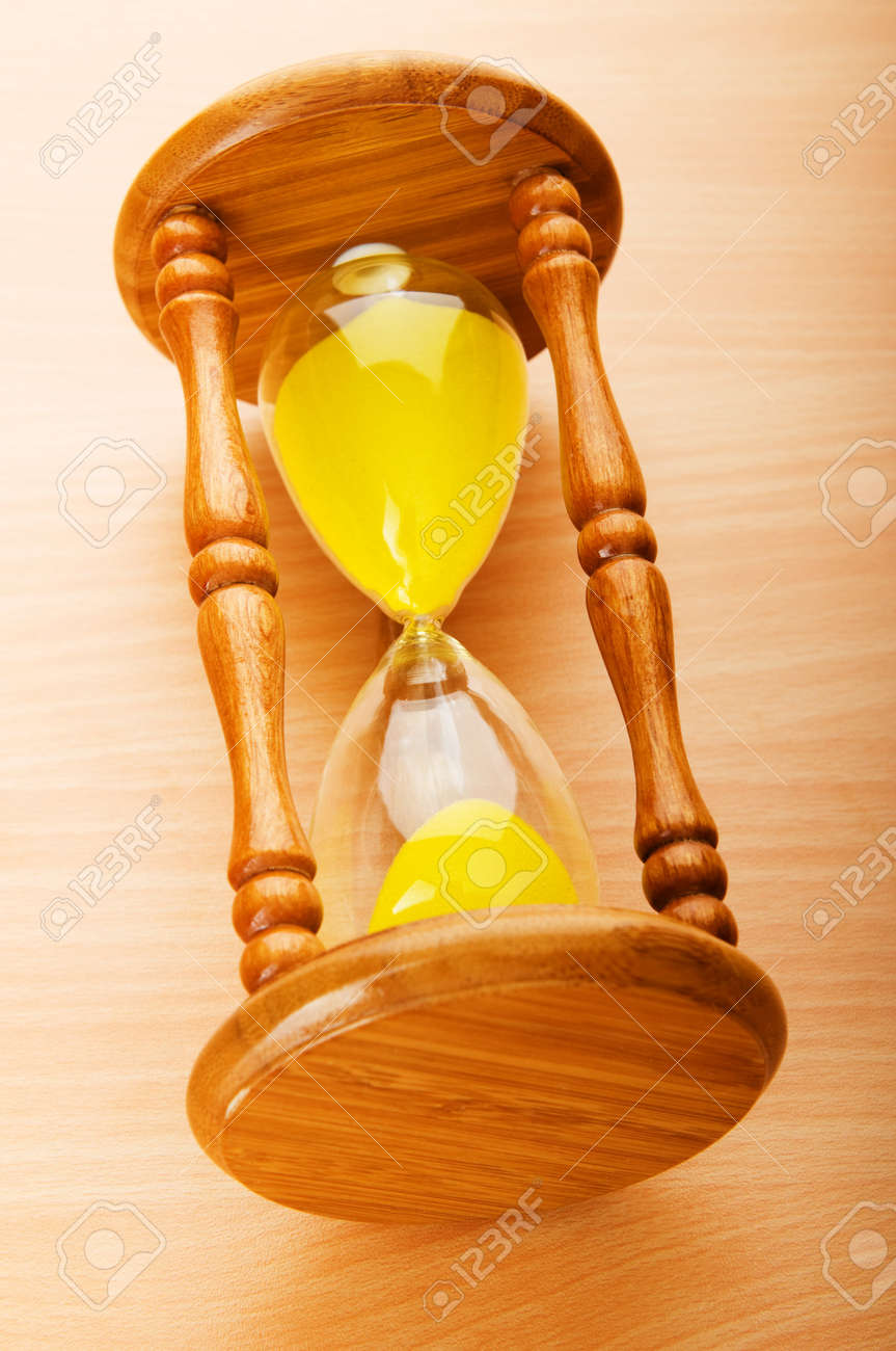Time concept - hourglass against the wooden background Stock Photo - 8054852