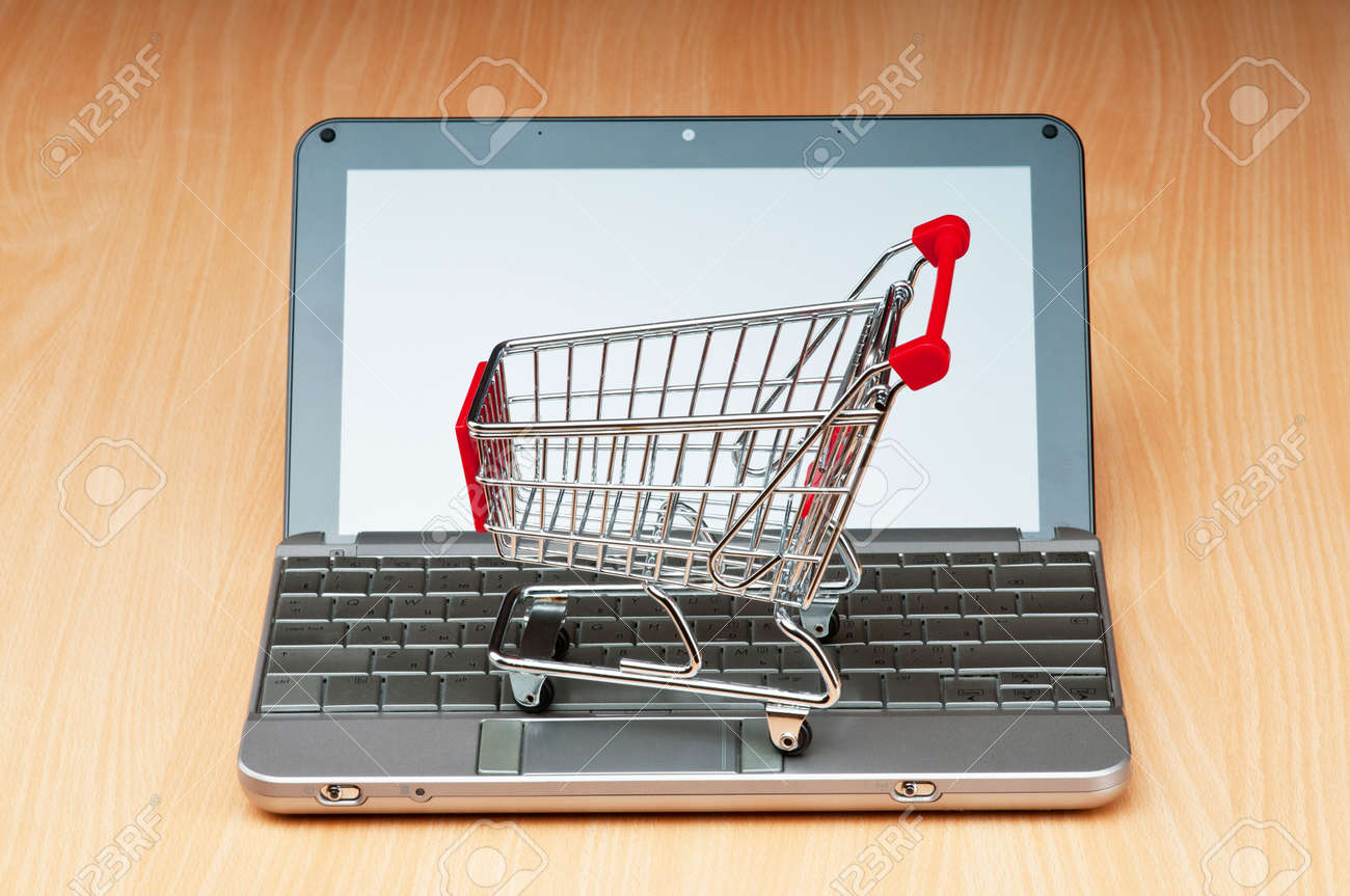Internet online shopping concept with computer and cart Stock Photo - 9847571