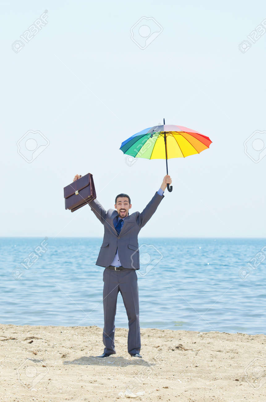 Man with umbrella on beach Stock Photo - 14385690