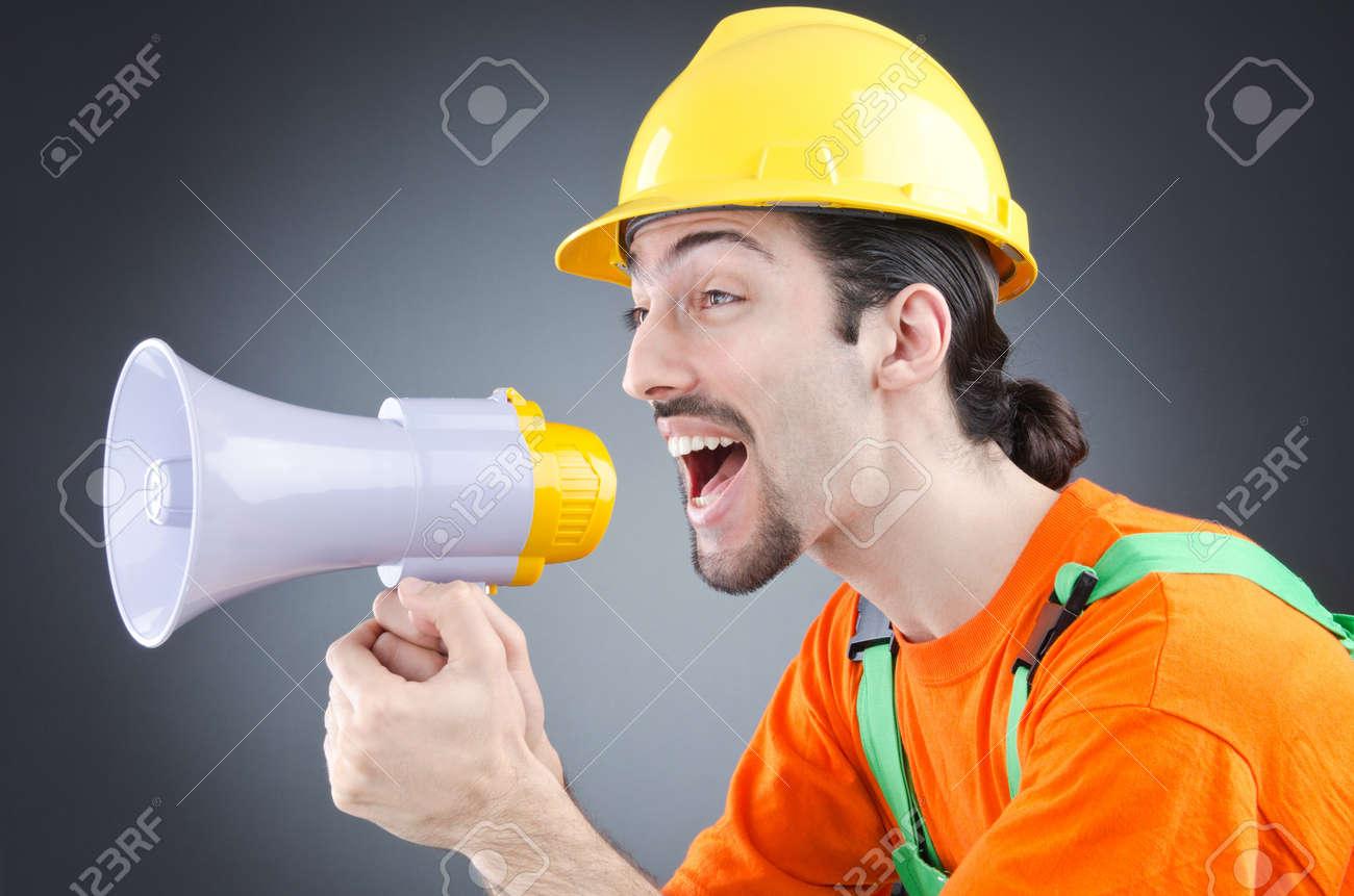 Construction worker with loudspeaker in studio Stock Photo - 14770107