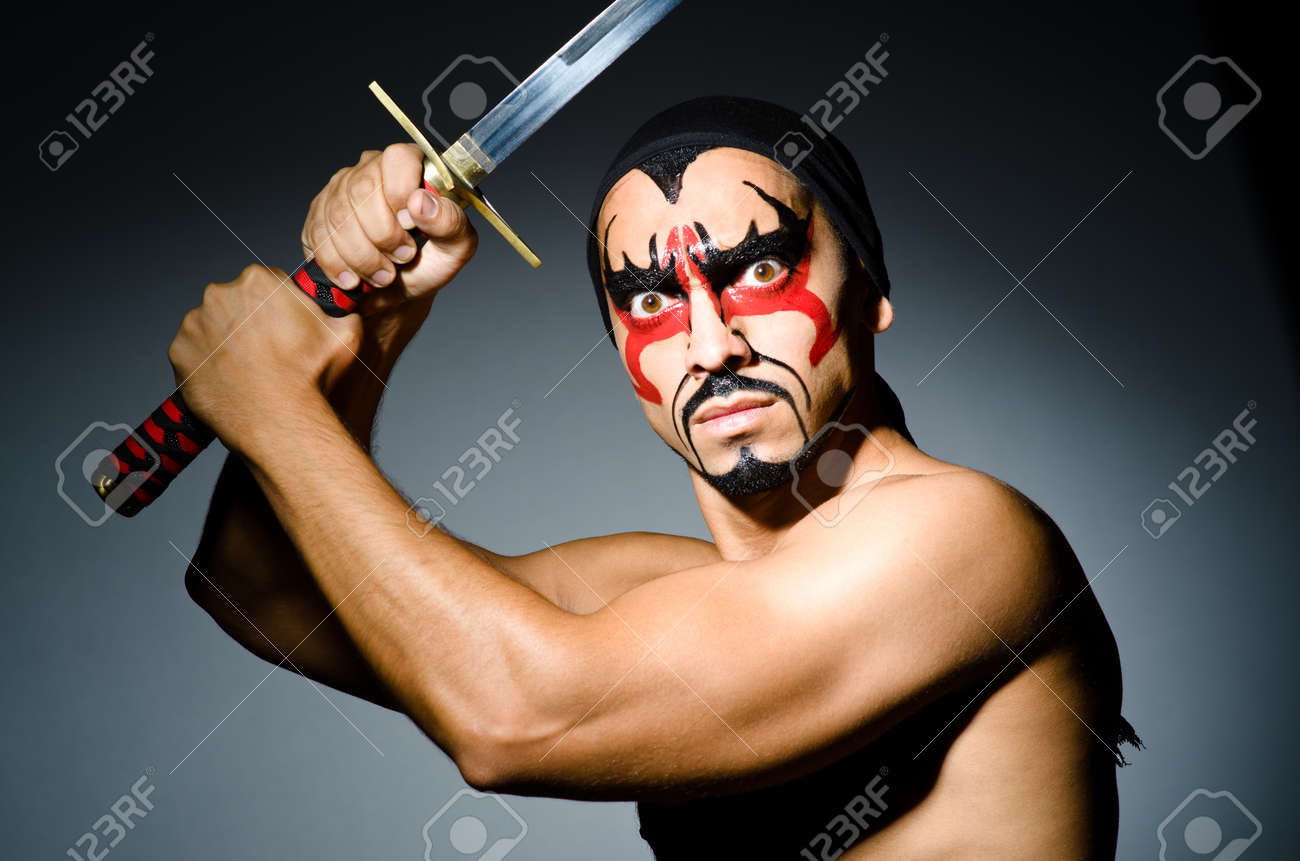 Man with sword and face paint Stock Photo - 22327765