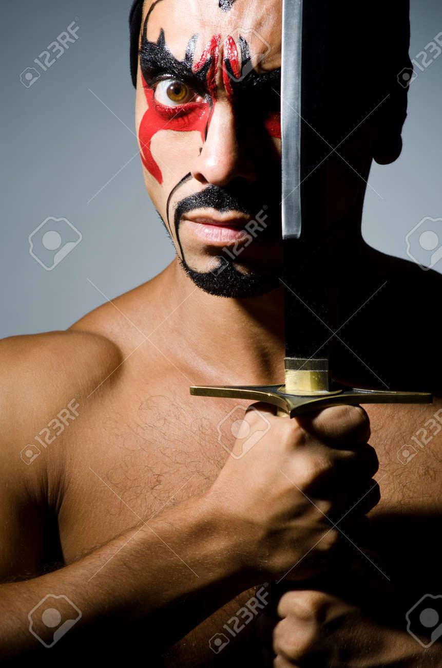 Man with sword and face paint Stock Photo - 22327766