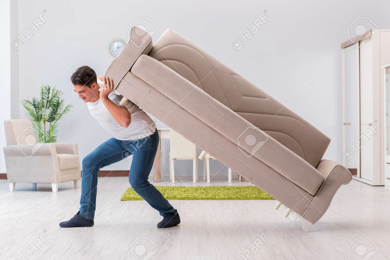 Man moving furniture at home - 67522834