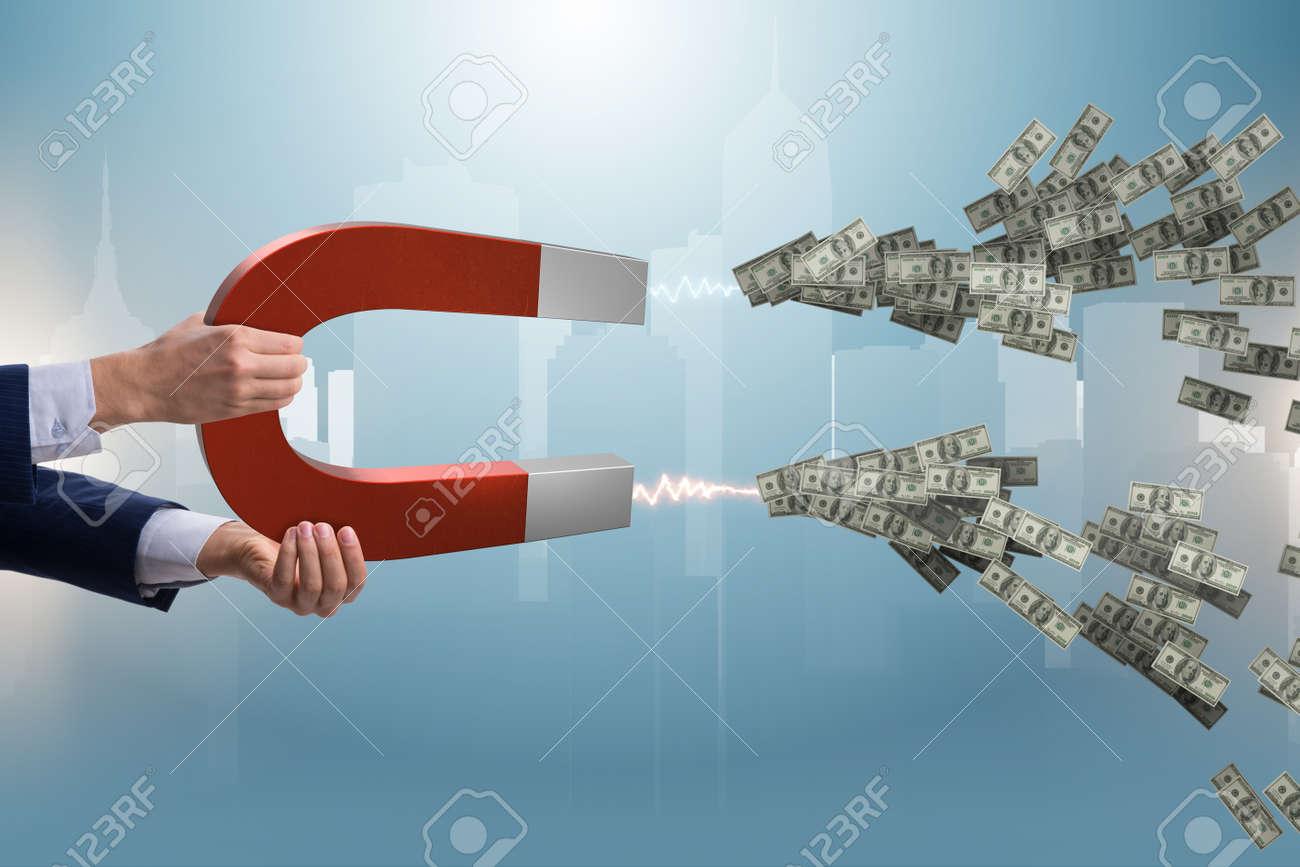 Businessman catching dollars on horseshoe magnet - 90164753