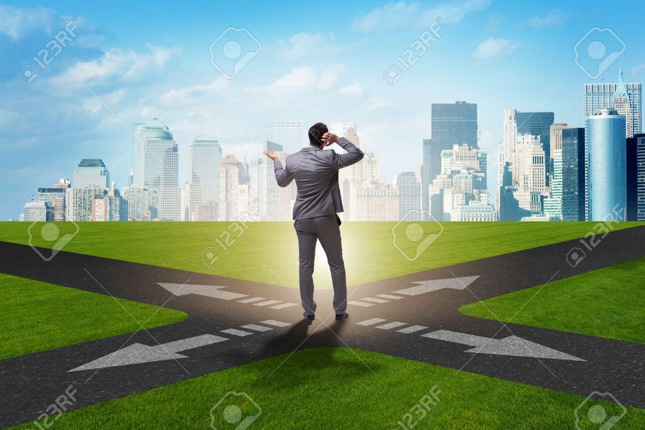 Young businessman at crossroads in uncertainty concept - 94282501