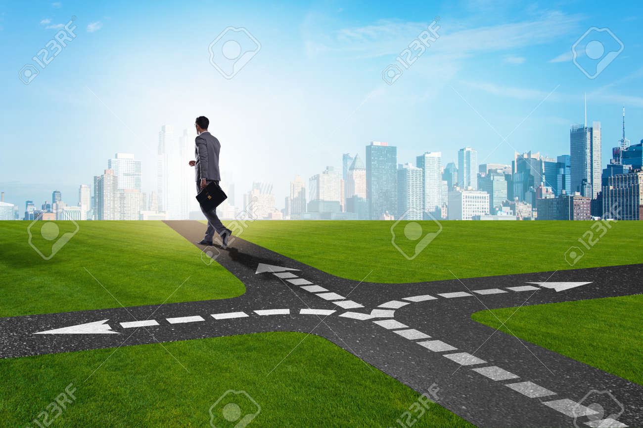 Young businessman at crossroads in uncertainty concept - 96359027