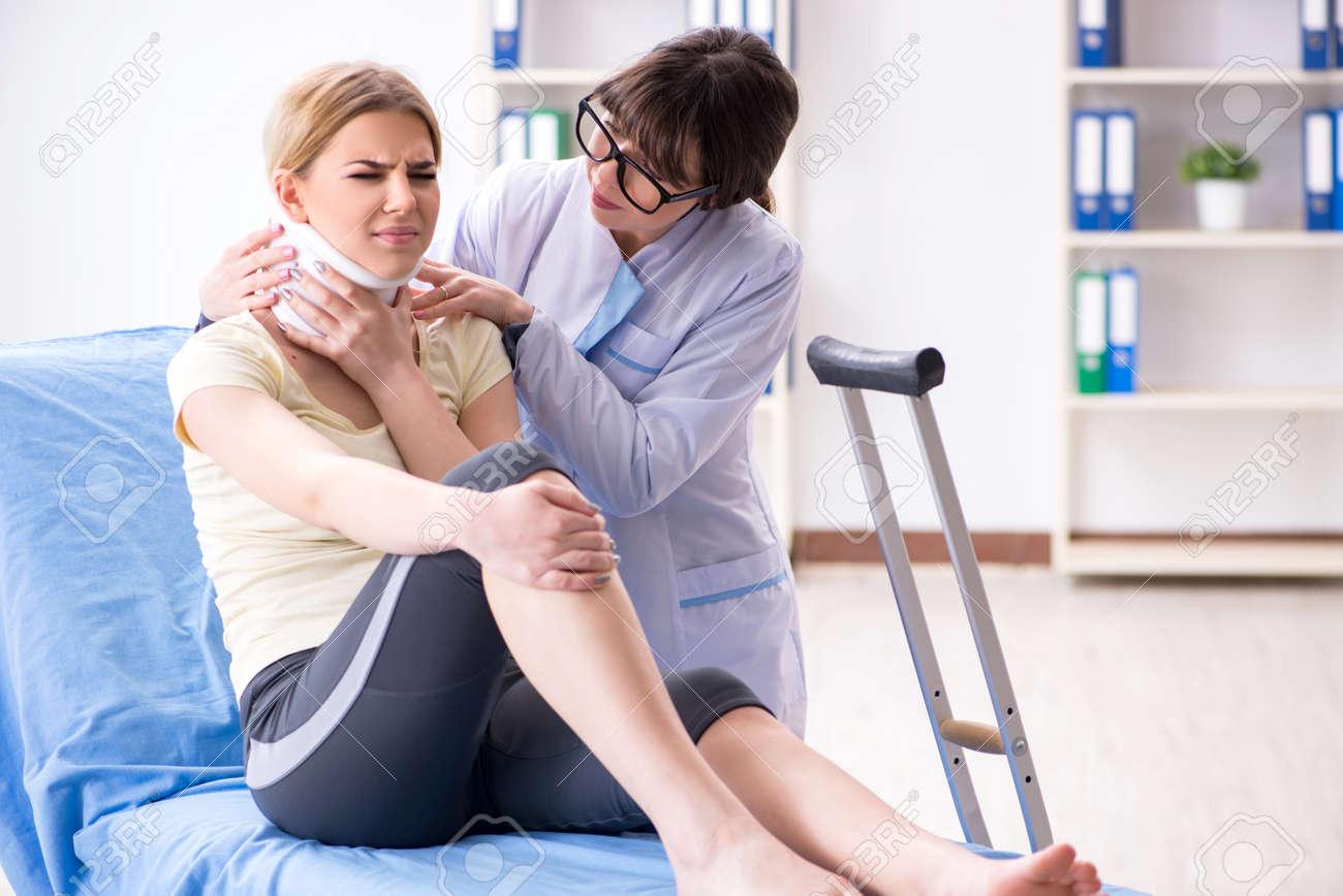 Doctor examining injured woman in hospital - 102984736