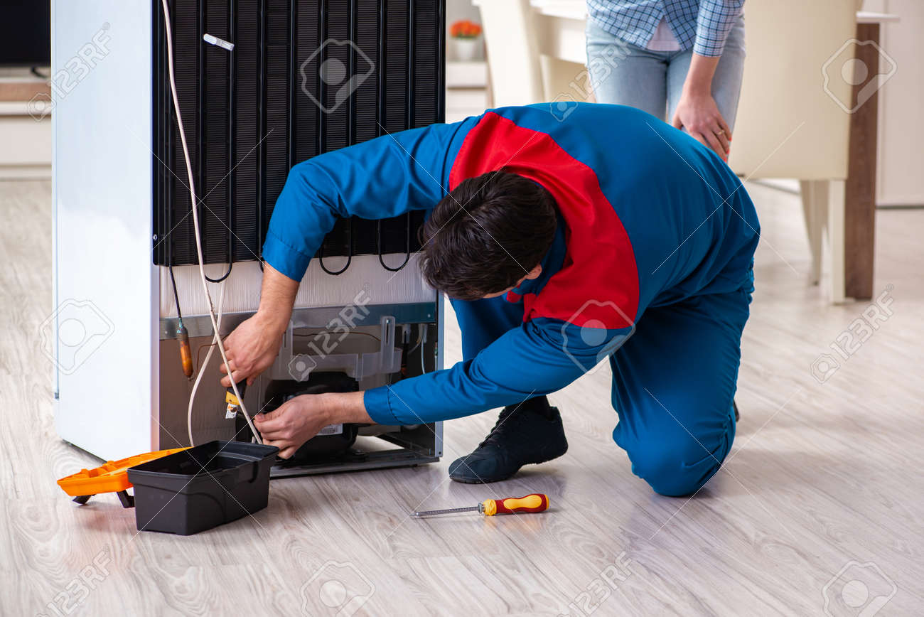 Man repairing fridge with customer - 104829921