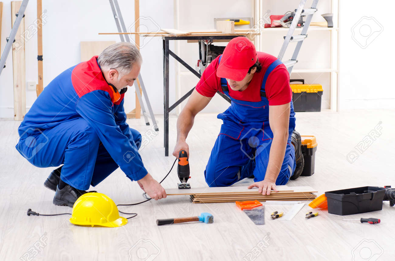 Two Professional Contractors Laying Flooring At Home Stock Photo