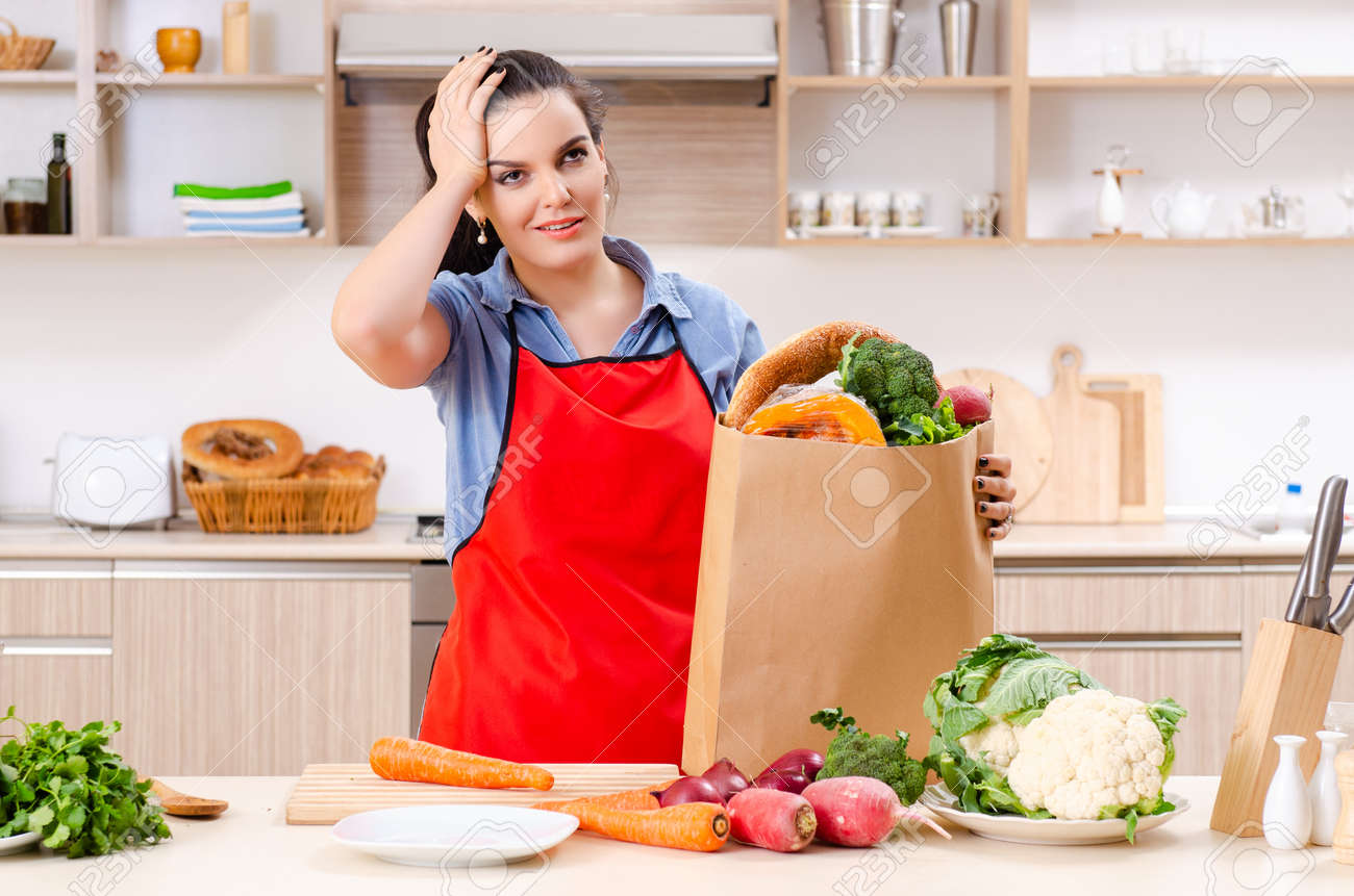 Young woman with vegetables in the kitchen - 121794268