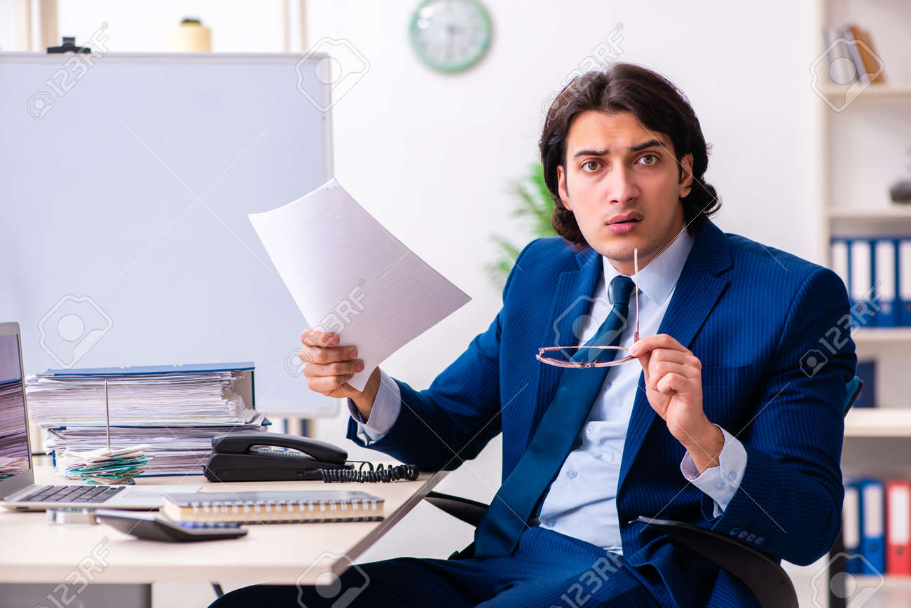 Young businessman sitting and working in the office - 126960444