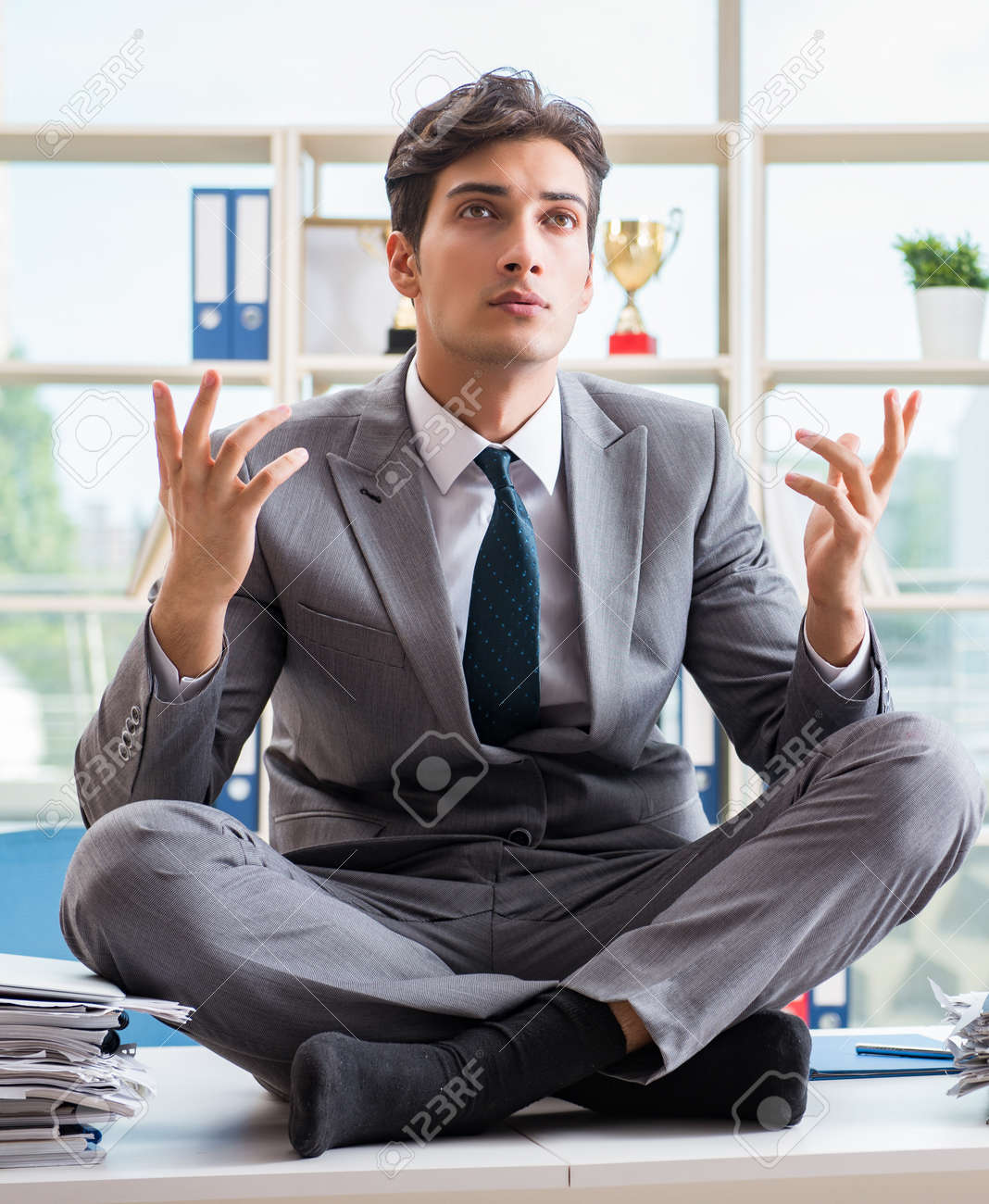 Businessman sitting on top of desk in office - 127012466
