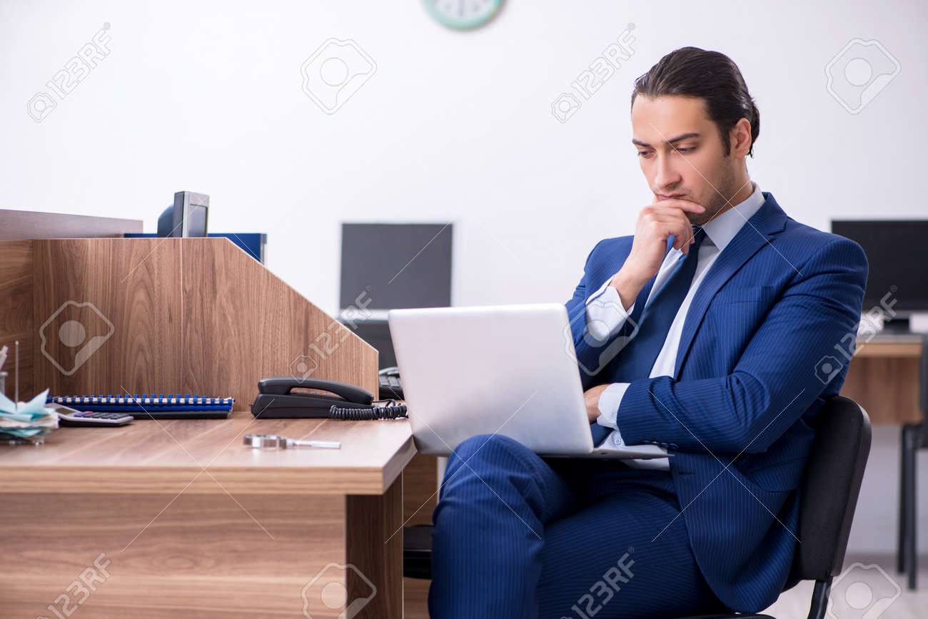 Young handsome businessman working in the office - 129701250