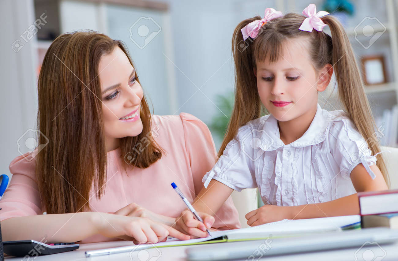 Mother helping her daughter to do homework - 133663374