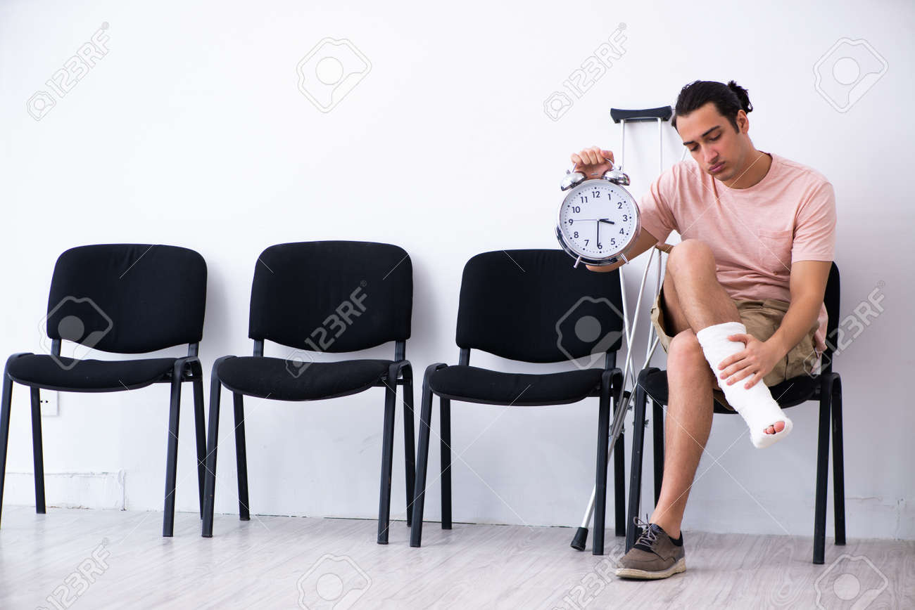 Young injured man waiting for his turn in hospital hall - 135261631