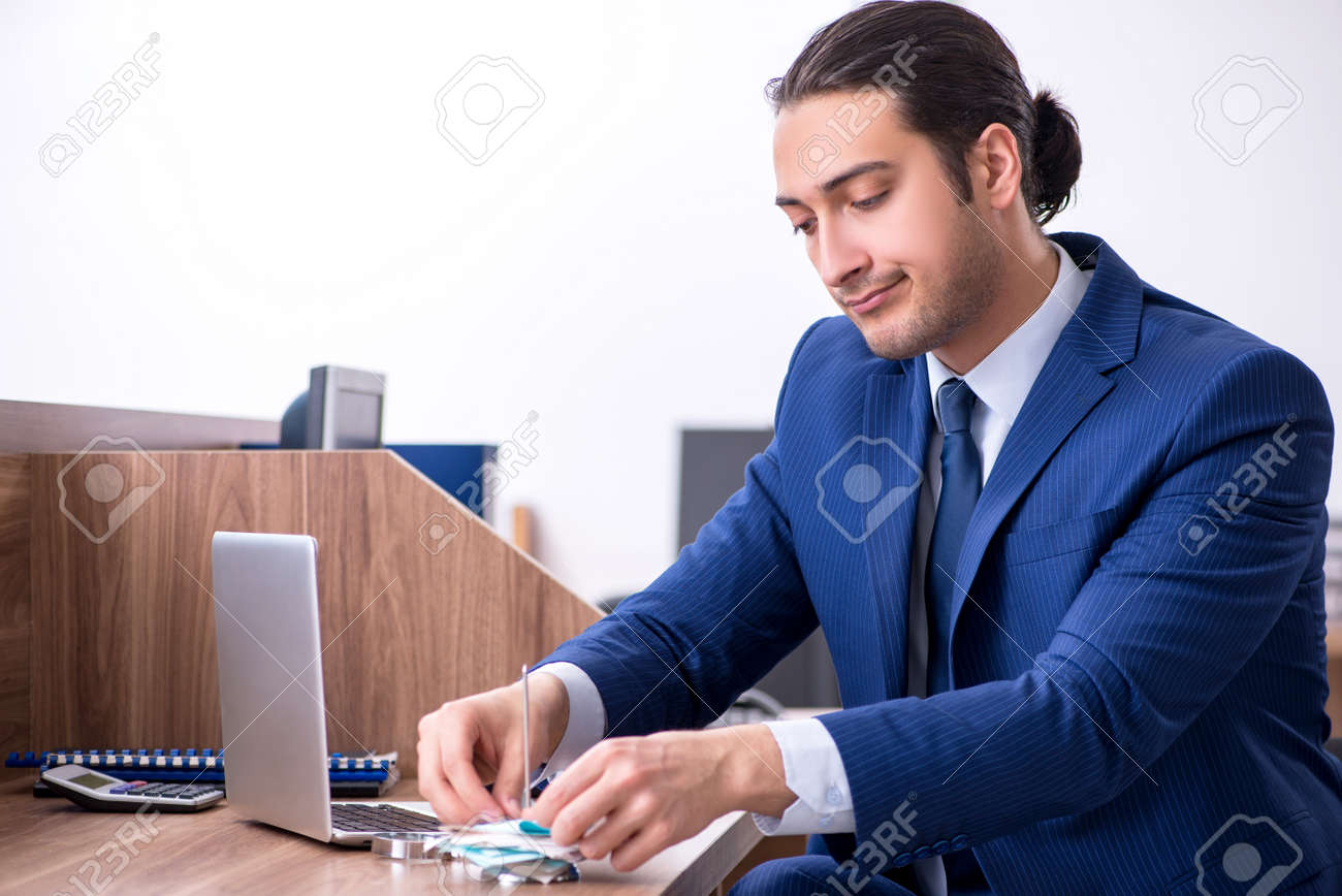 Young handsome businessman working in the office - 137055394