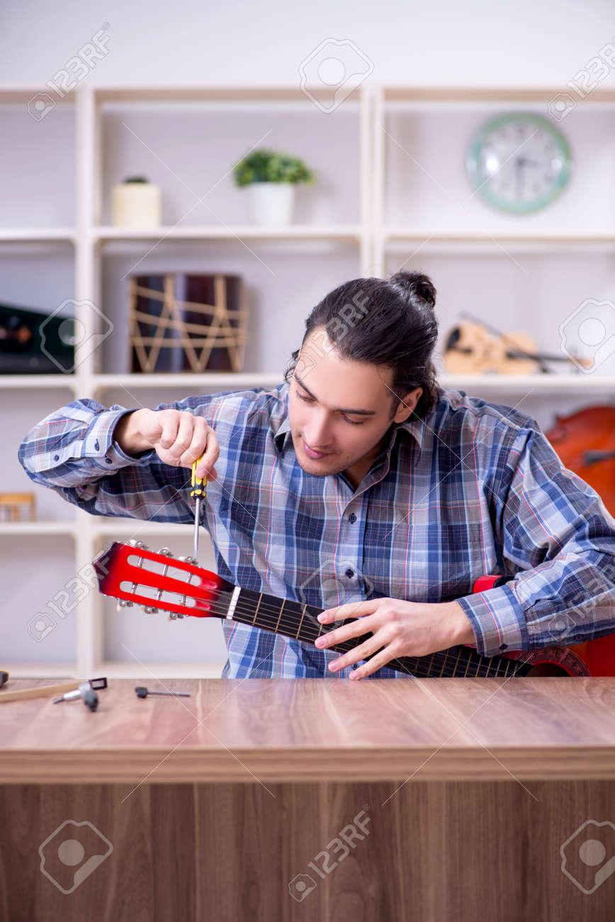 Young handsome repairman repairing guitar - 137054634