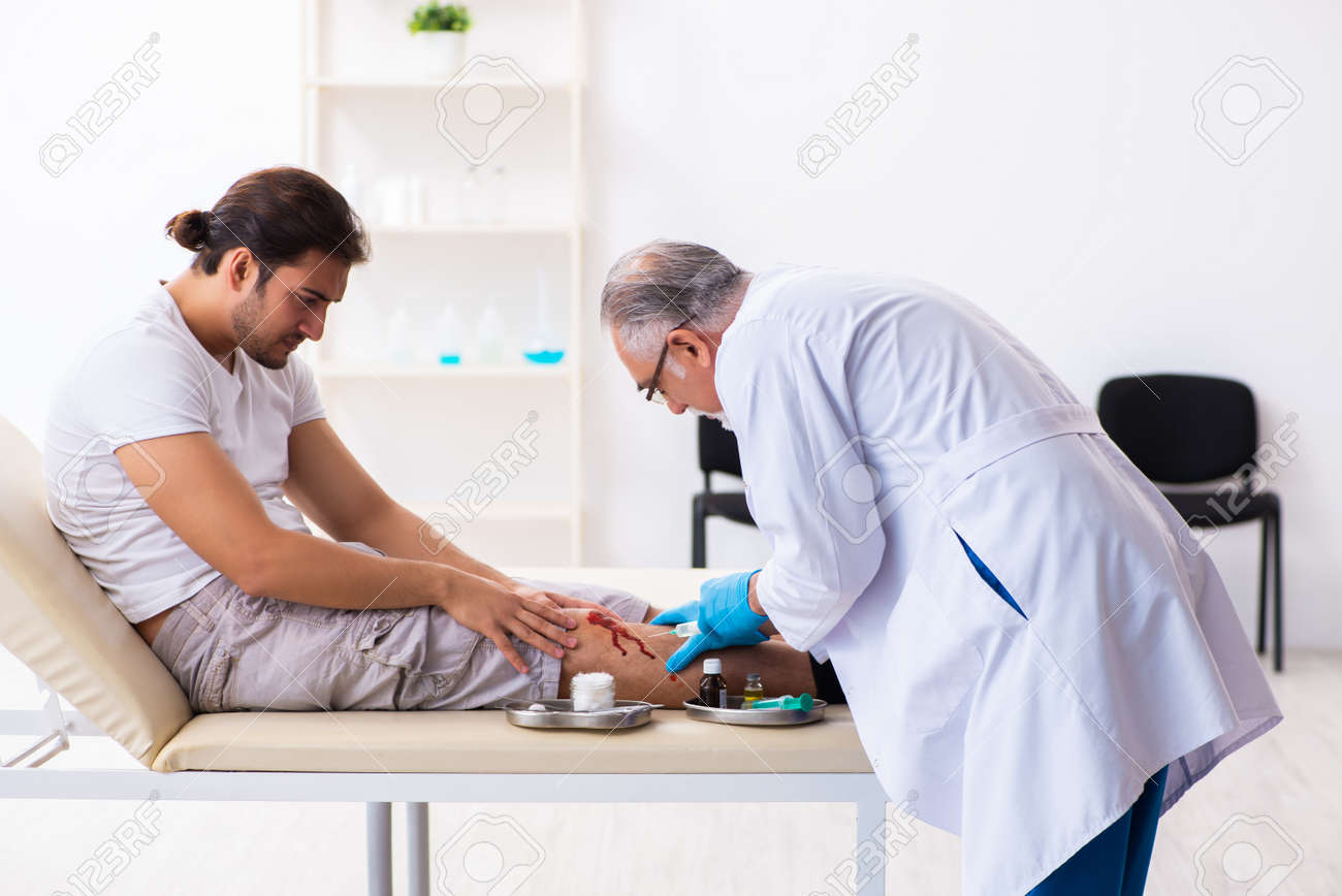 Leg injured man visiting old doctor in first aid concept - 145690794