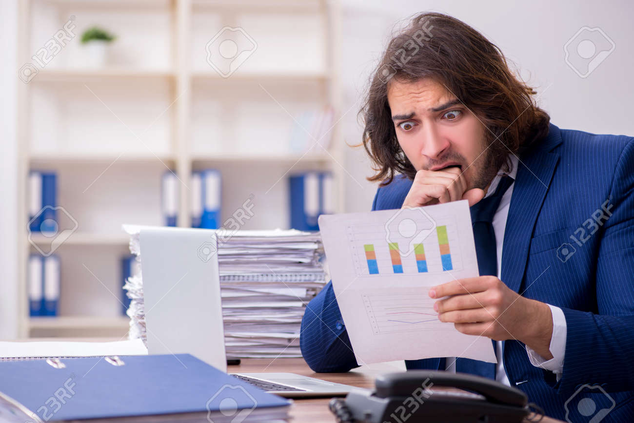 Young male employee unhappy with excessive work - 146403923