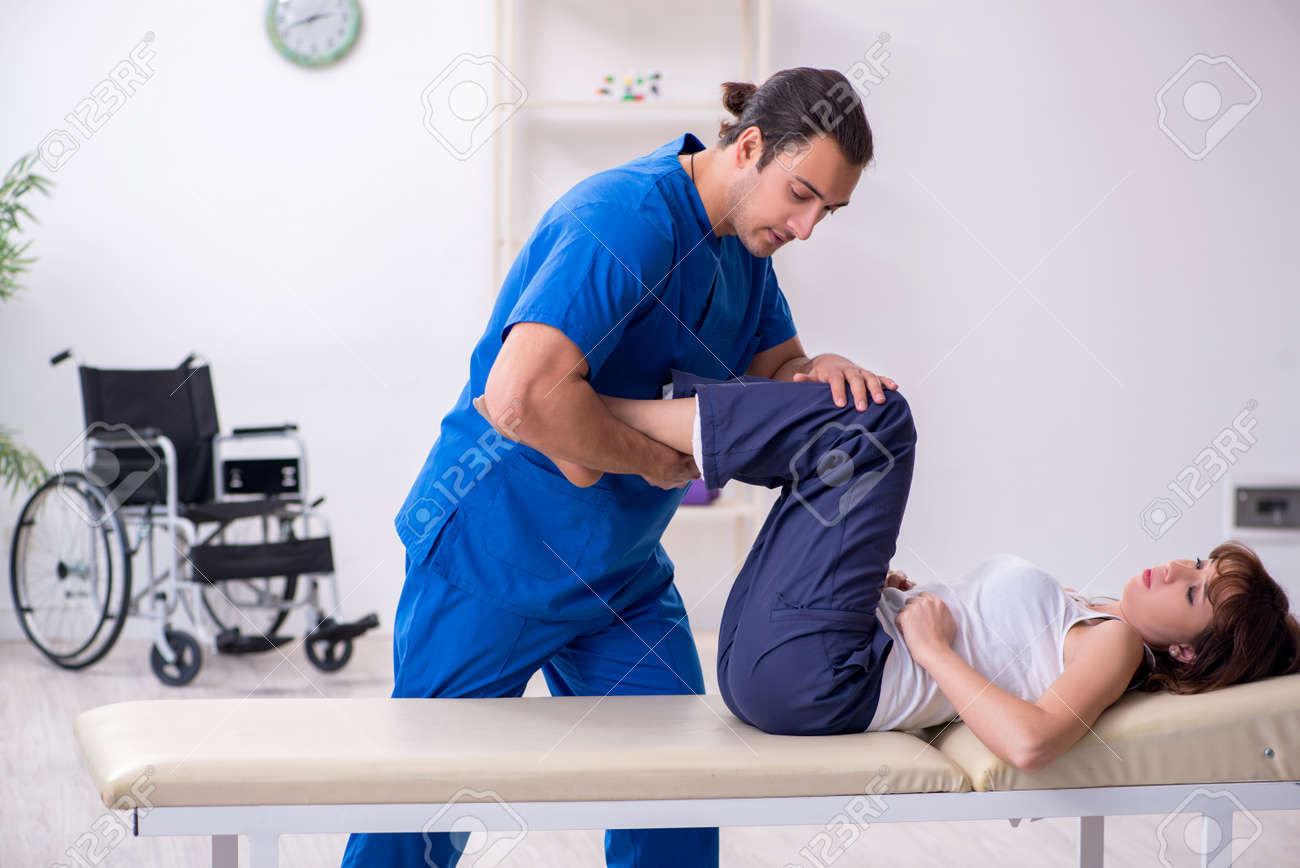 Injured woman visiting young male doctor osteopath - 149914736